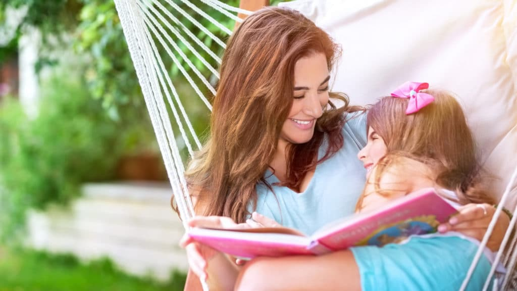 mom reading to child outside